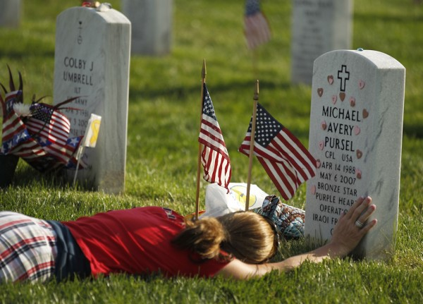 "A  mourner, believed to be Air Force Reserve Captain Teresa Dutcher lays at the grave of Corporal Michael Avery Pursel at Arlington National Cemetary in Arlington, Virginia.  She visits the cematery at the conclusion of the ""Flags In"" on May 24, 2012.   Each year for the past 40 years, the 3rd U.S. Infantry or ""Old Guard"" honors America's war dead by placing American flags at the gravestones of service members buried at Arlington National Cemetery prior to Memorial Day weekend.   The tradition, known as ""flags in,"" is conducted annually by the 3rd U.S. Infantry, the Army's official ceremonial unit. Every available soldier in the 3rd U.S. Infantry participates, placing a small American flag one foot in front and centered before each grave marker over a three-hour period.  During this time, the soldiers place flags in front of more than 260,000 gravestones."